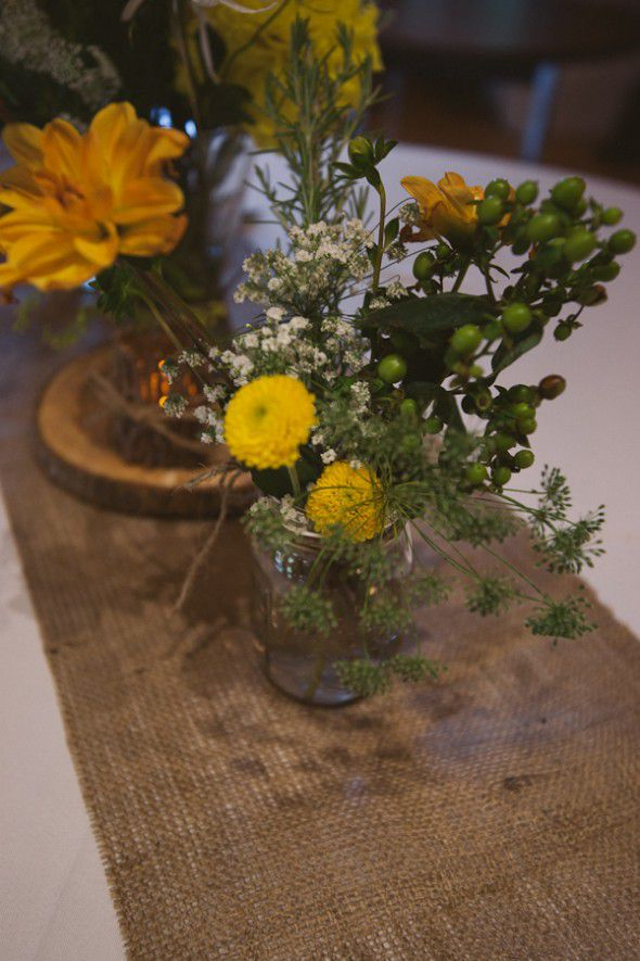 A burlap table runner at rustic wedding