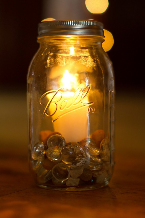 A mason jar used as a candle holder with rocks