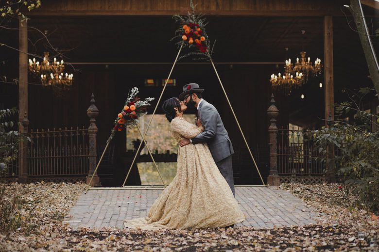 bride and groom kissing in front of barn wedding venue