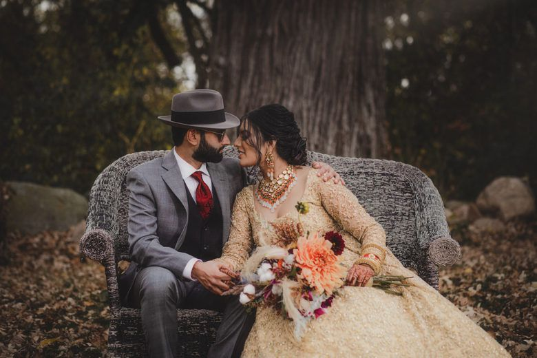 Bride and groom sitting on bench in woods