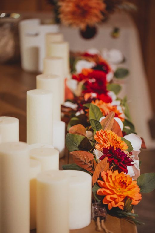 candle pillars and flowers on table