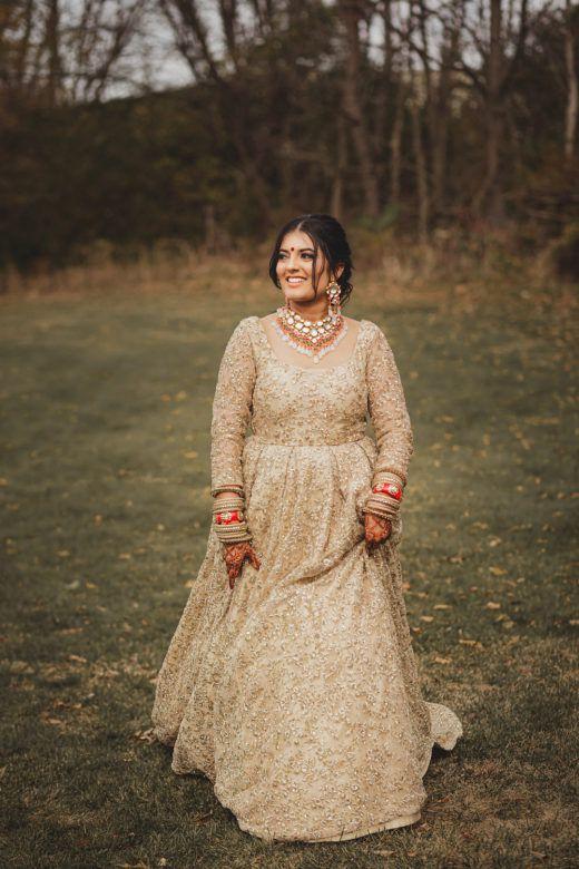 Bride smiling in field wearing gold long dress