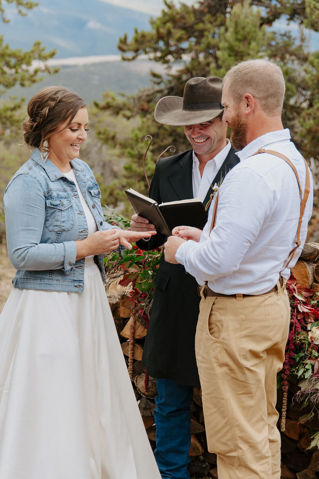 Bride and groom putting on rings at mountain elopement ceremony