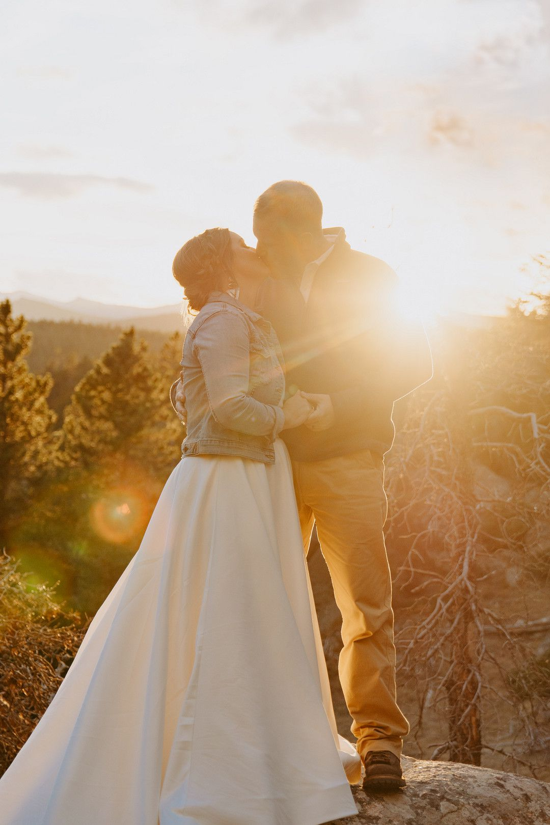 Bride and Groom kissing on mountains at sunset