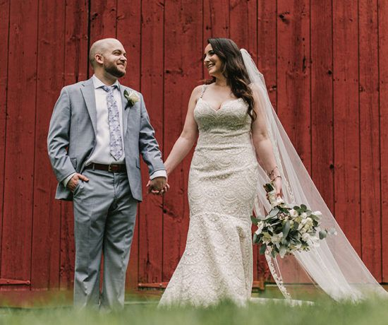 Bride and groom smiling holding hands in front of barn wedding venue
