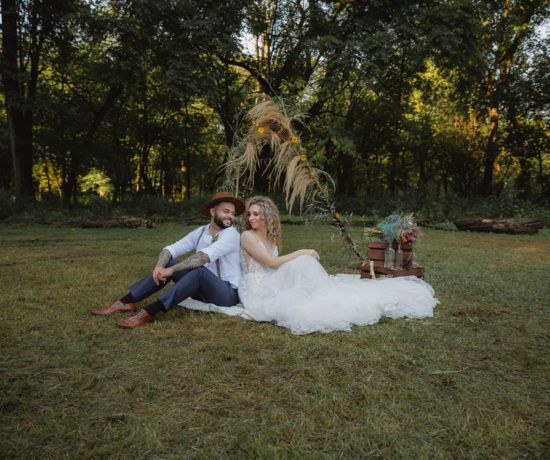 Bride and groom sitting on ground in front of ceremony alter
