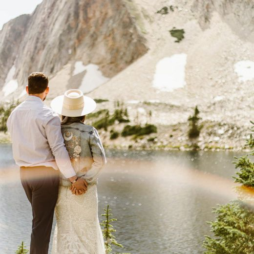 bride and groom looking over a mountain with a rainbow