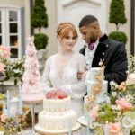 bride and groom smiling in front of table weith desserts from bridgerton netflix styled wedding shoot