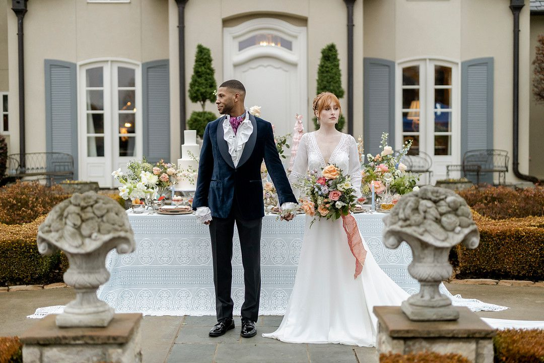 bride and groom holding hands in front of mansion