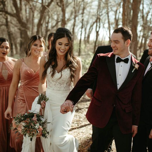 bride, groom, and bridal party laughing and smiling