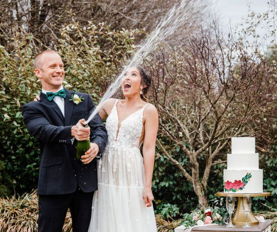 bride and groom popping champagne