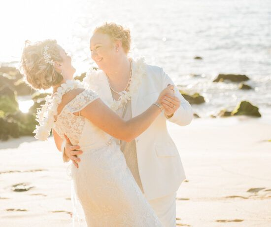 bride and bride dancing on the beach in maui