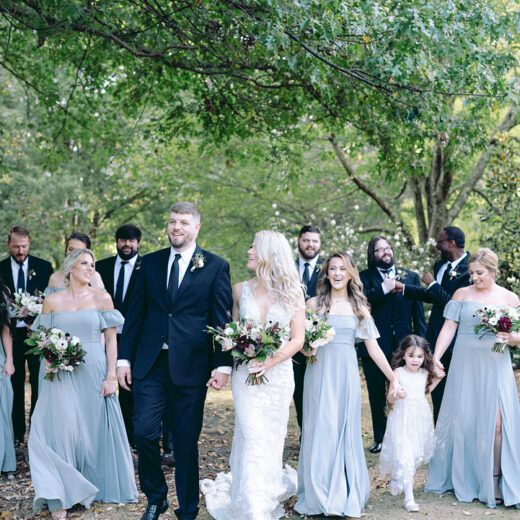 full bridal party walking through garden