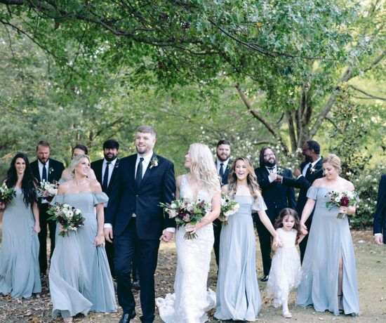 full bridal party walking through garden