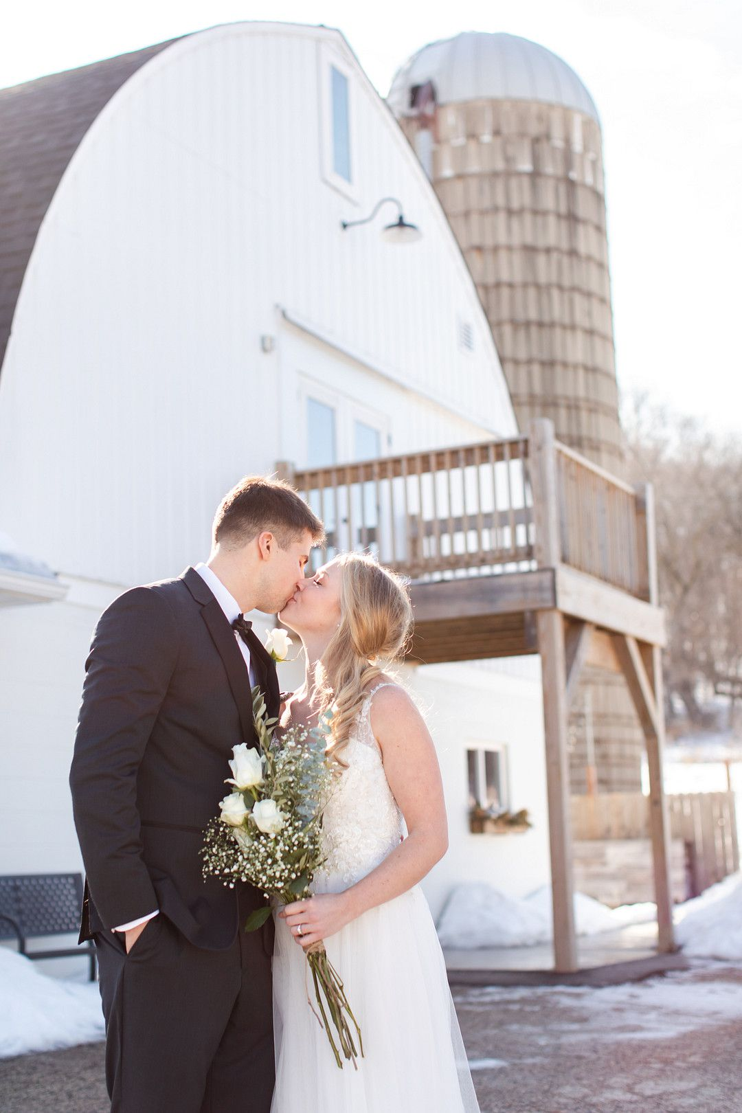bride and groom kissing in front of white barn