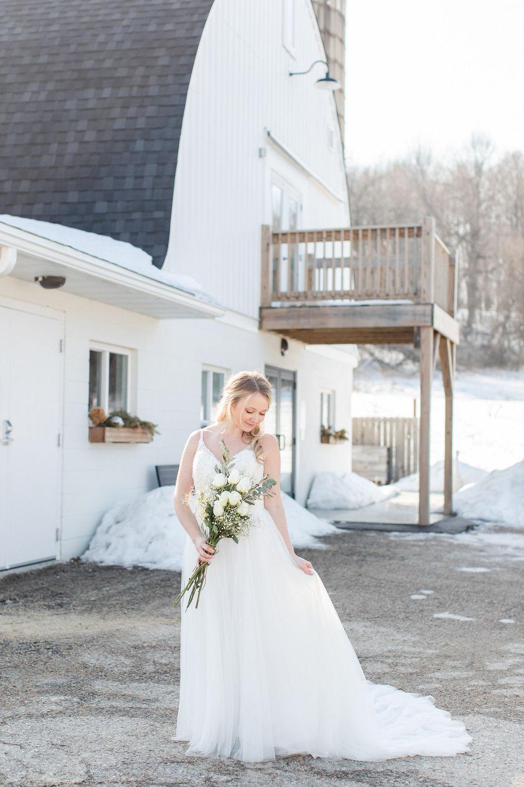 bride in wedding dress in front of barn
