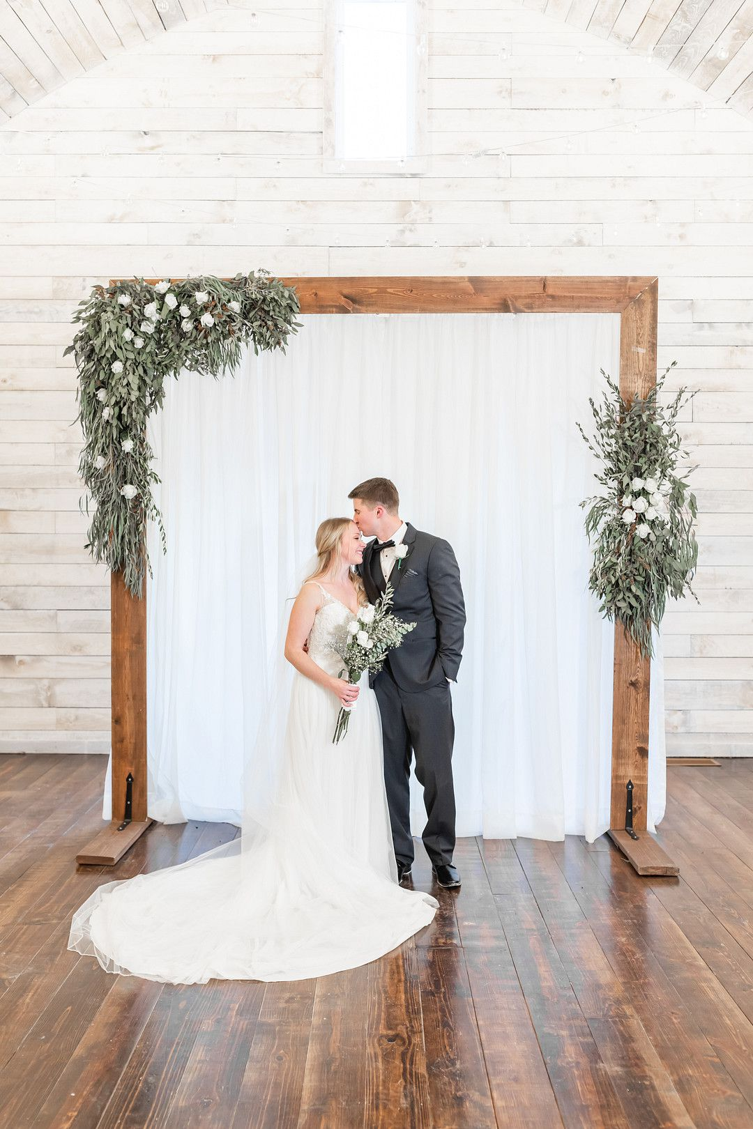 bride and groom under winter wedding altar