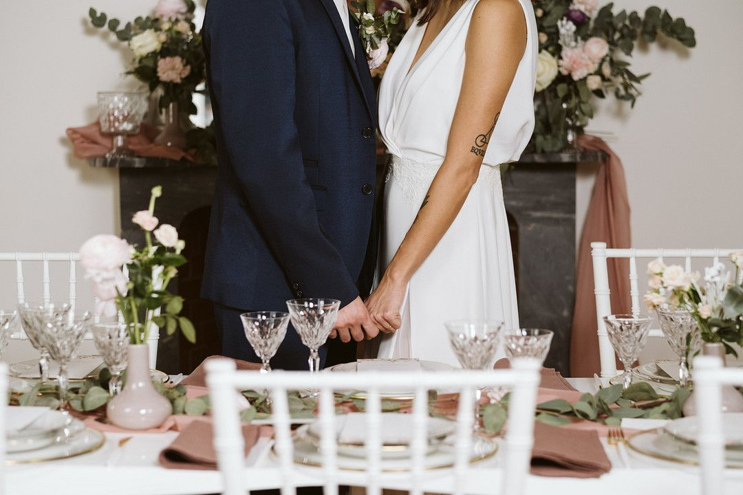 bride and grooms holding hands at at home elopement wedding table