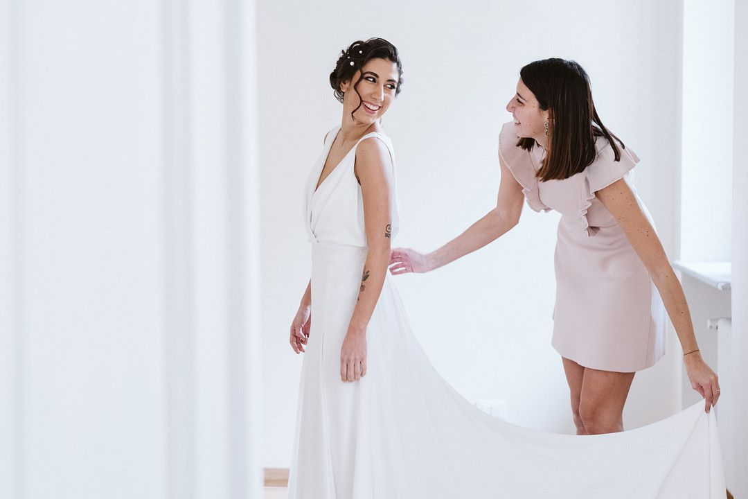 bridesmaid helping bride with dress