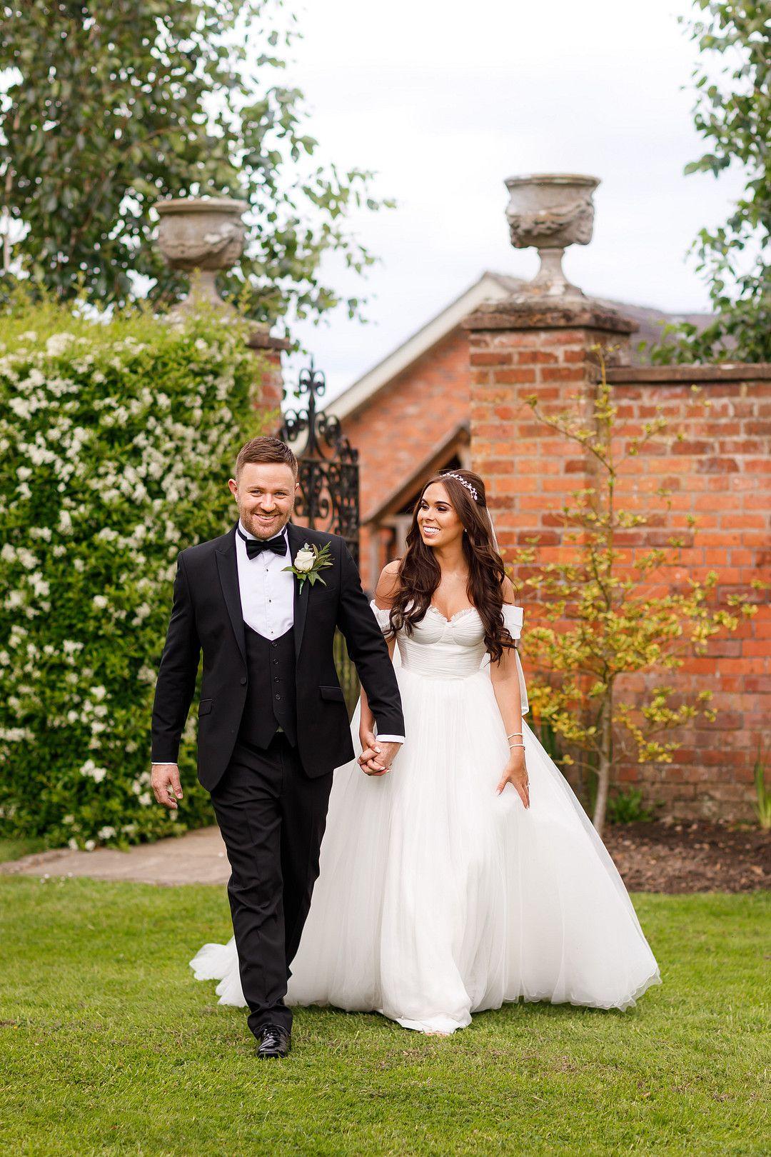 bride and groom at elegant summer wedding walking hand in hand