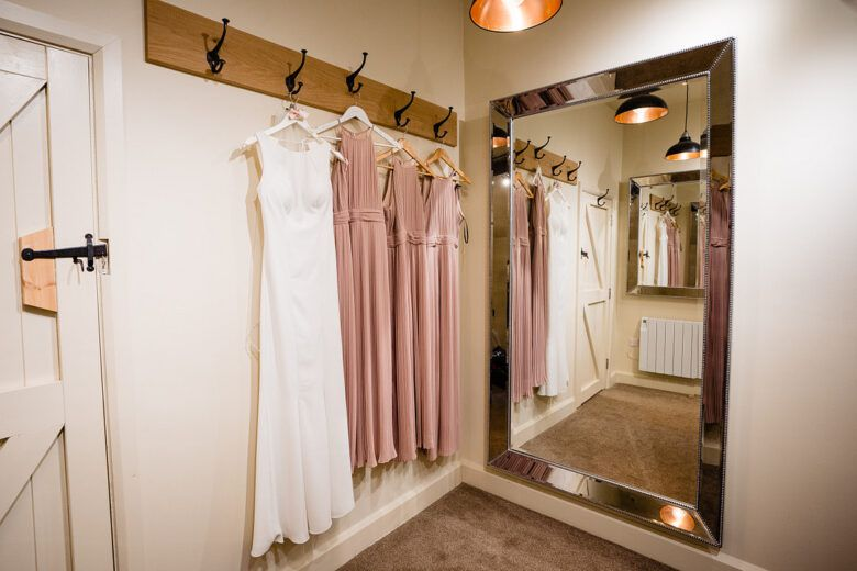 wedding and bridesmaid dresses hanging in bridal suite
