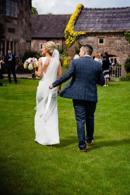 groom holding brides veil as she walks