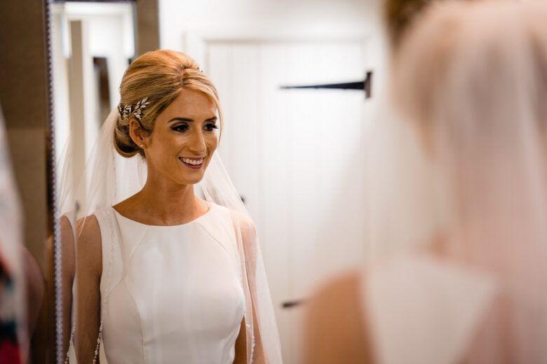bride dressed for wedding looking in mirror