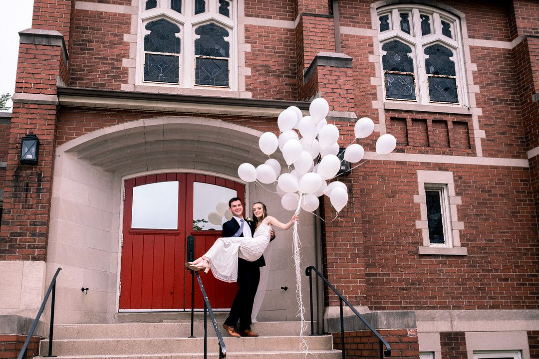 groom holding bride who has balloons in her hand