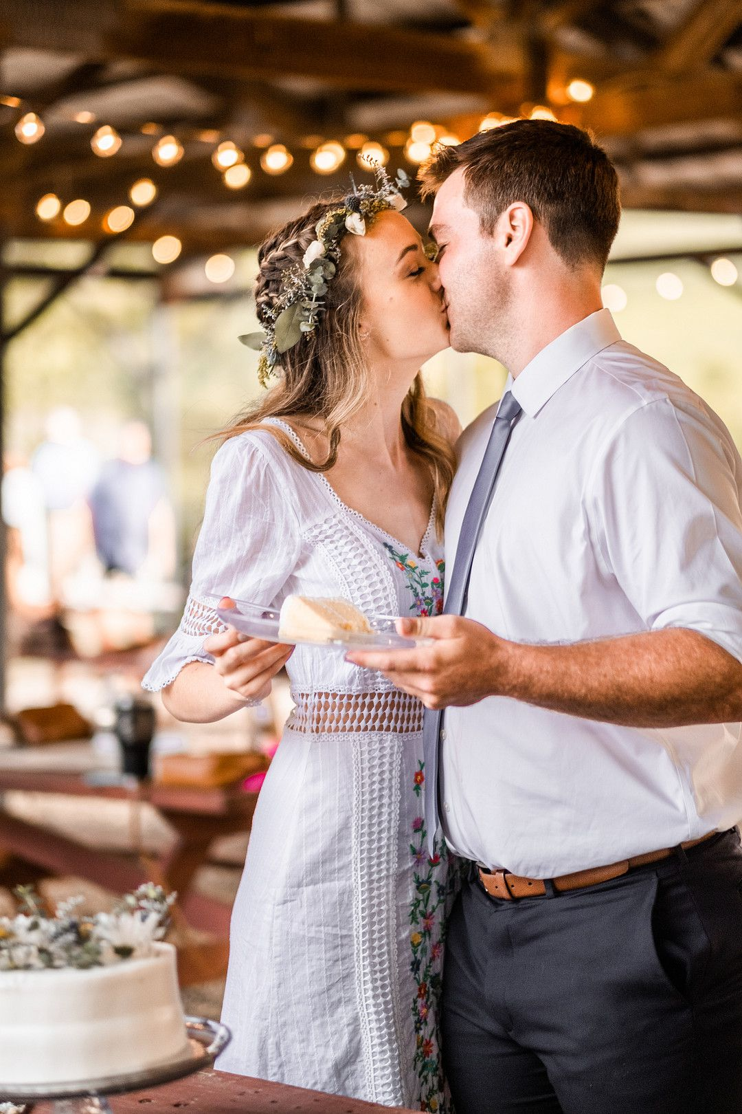 bride and groom kissing and eating cake