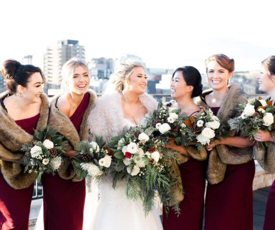winter bridal party with bridesmaids wearing faux fur bridesmaid wraps